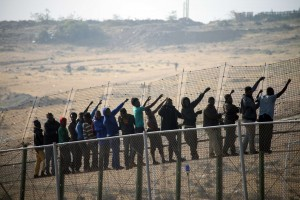 Migranti sulla recinzione   (afp)